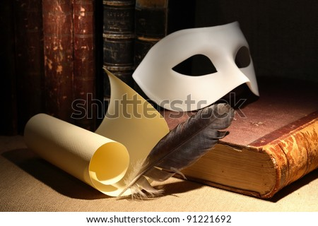 Dramatic concept. Vintage still life with quill and scroll near mask and old books on dark background - stock photo