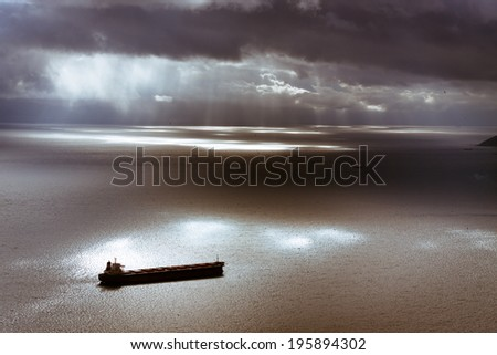 Dramatic dark moody sky and Mediterranean Sea landscape with ship leaving Gibraltar harbor. - stock photo