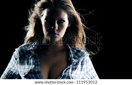 Dramatic dark portrait of a sexy beguiling woman with her shirt unbutttoned to reveal her cleavage - stock photo