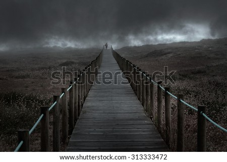 Dramatic dark wooden walkway over a foggy dune in an overcast evening. Used some digital filters. - stock photo