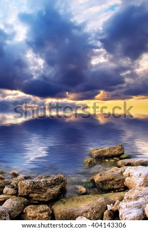 Dramatic dawn on the sea. The rising sun on the background of the sea and stones. Natural composition - stock photo