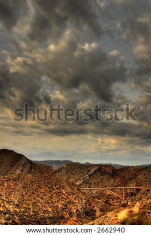 Dramatic desert mountains with a storm approaching a bridge crossing