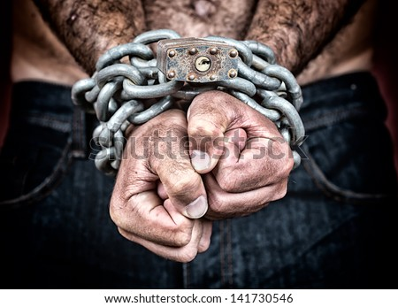 Dramatic detail of the chained hands of an adult man (with a strong chain and padlock) - stock photo