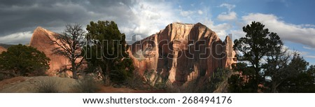 Dramatic evening panoramic sunset of a red rock sandstone canyon wall in Kolob - Zion National Park, Utah, USA - stock photo