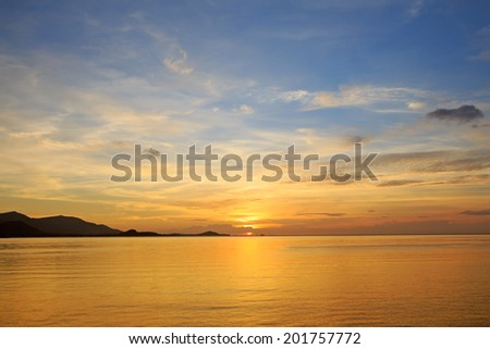 Dramatic golden beach sunset sky and tropical sea background - stock photo