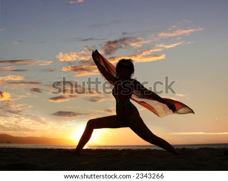 Dramatic image of a woman by the ocean at sunset