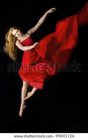 Dramatic image of a woman wearing red dress  jumping over  on a black background - stock photo