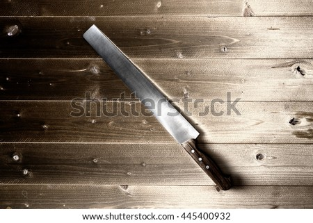 dramatic image of knife on raw wooden background  - stock photo