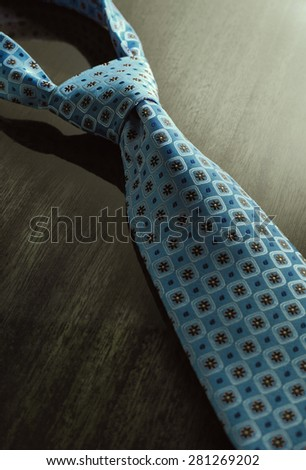 Dramatic image of necktie on the wooden table - stock photo