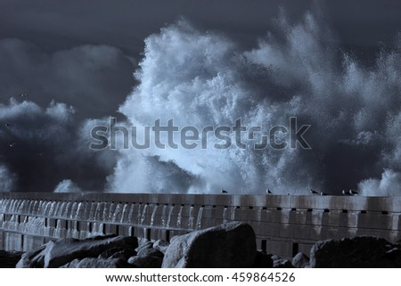 Dramatic infrared ocean storm with big waves over pier. North of Portugal. Toned blue. - stock photo
