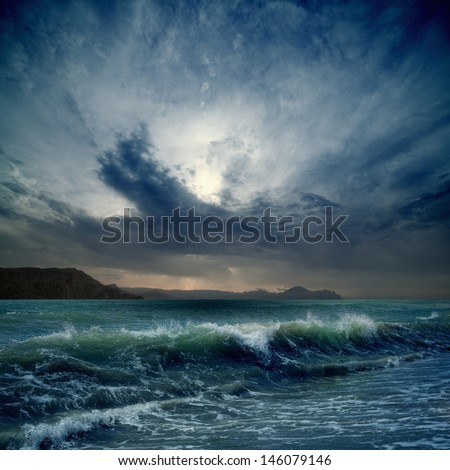 Dramatic landscape - dark stormy sky, sea waves, mountains - stock photo