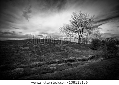 Dramatic landscape image of an ominous sky behind a small hill with a single, leafless tree, shot in black and white. - stock photo