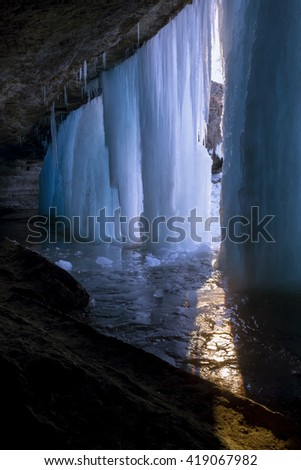 Dramatic Light of the Caves and Frozen Winter Waterfalls during Sunset
