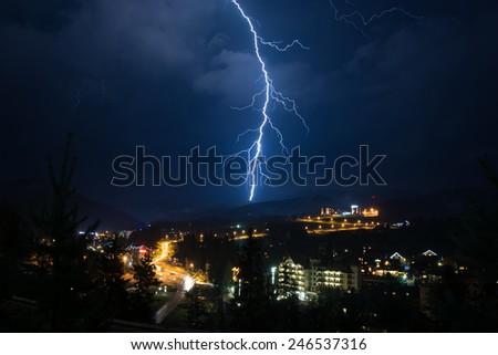 Dramatic lightning strike over mountains resort - stock photo