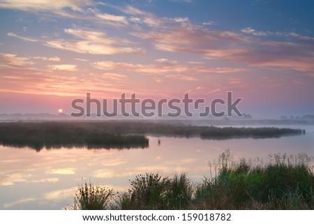 dramatic misty sunrise over river, Drenthe, Netherlands - stock photo