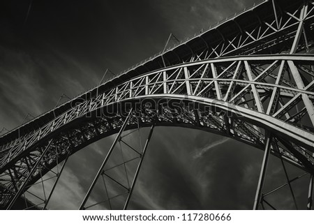 Dramatic monochrome photo of Dom Luis Bridge, Porto - Portugal. The bridge is in two levels and connect the two parts of the city witch the Douro river divide. - stock photo