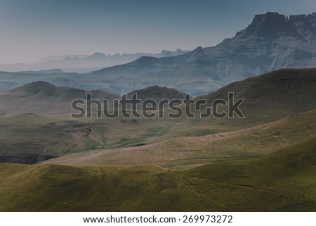 Dramatic mountain range and rolling hills stretching into the distance in the Drakensberg, Kwazulu-Natal, South Africa - stock photo