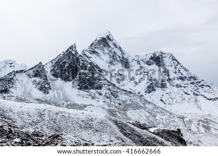 Dramatic mountain view of Ama Dablam after a heawy snowfall on the famous Everest Base Camp trek in Himalayas, Nepal. Dramatic mountain monochrome landscape on a cloudy day. - stock photo