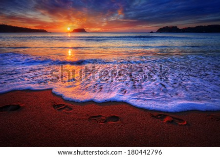 Dramatic ocean sunrise with foot prints in the sand - stock photo