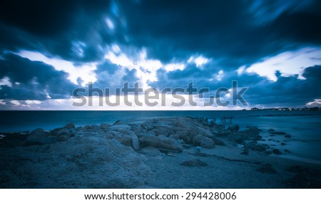 Dramatic orange sunset in the Mediterranean Sea, the pier was destroyed by storms. tinted - stock photo