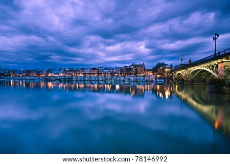 Dramatic panorama of Seville riverside at down and the Triana Bridge, the oldest bridge of Seville. - stock photo
