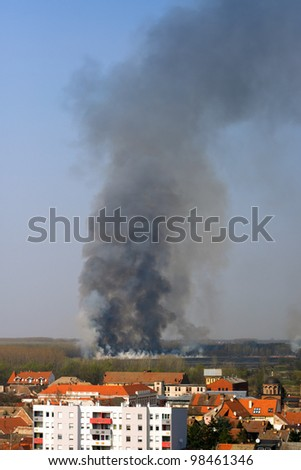 Dramatic photo of forest fire approaching European town - stock photo