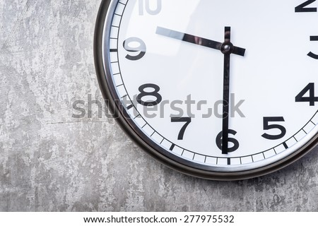 Dramatic picture of round wall clock hanging on the grey concrete wall - stock photo