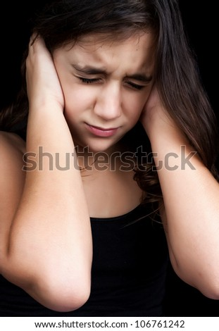 Dramatic portrait of a frightened girl with a very emotional expression isolated on a black background