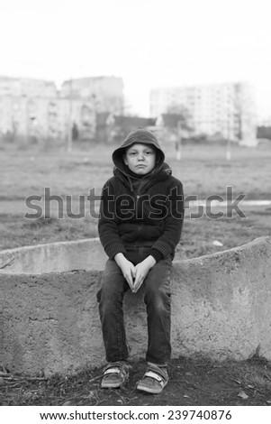 dramatic portrait of a little homeless boy - stock photo