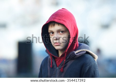 dramatic portrait of a little homeless boy, poverty, city, street