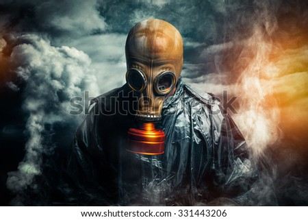 dramatic portrait of a man wearing a gas mask - stock photo