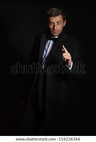 Dramatic portrait of a suave handsome man in a tuxedo and bowtie highlighted in darkness