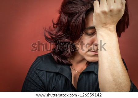 Dramatic  portrait of a woman suffering a headache or a strong depression with a dark red background - stock photo