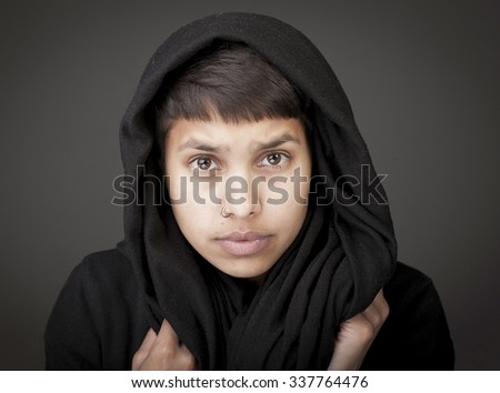 Dramatic portrait of a young woman wearing a black afghan scarf - stock photo