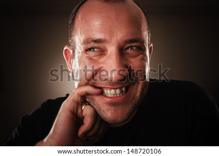 Dramatic portrait of adult man with sly facial expression, biting his fingernail - stock photo
