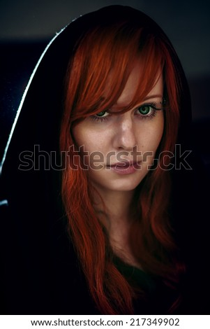 Dramatic portrait of beautiful red hair woman in black hood. Grain added for better impression. - stock photo