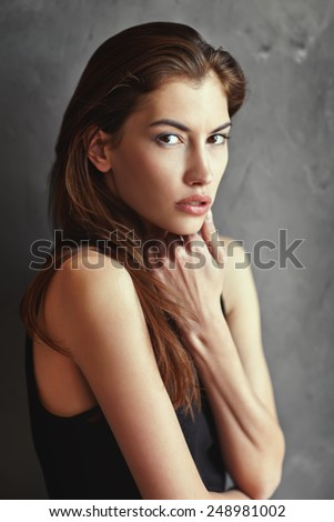 dramatic portrait of passion young woman on grunge wall background  - stock photo