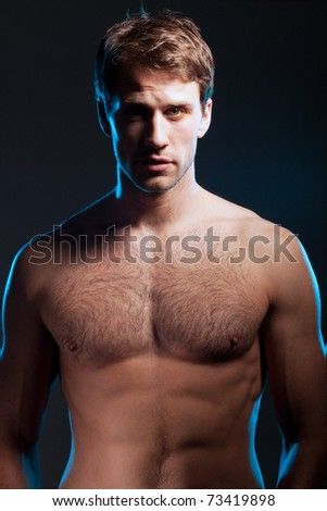 Dramatic portrait of young handsome fit man against dark background