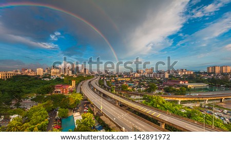 Dramatic scenery of the Kuala Lumpur city at sunrise with double rainbow - stock photo