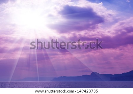 Dramatic   sea with sun rays and clouds in pink colors