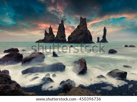 Dramatic seascape of Reynisdrangar cliffs in the Atlantic ocean. Colorful summer sunset in south Iceland, Vic village location, Europe. Artistic style post processed photo.