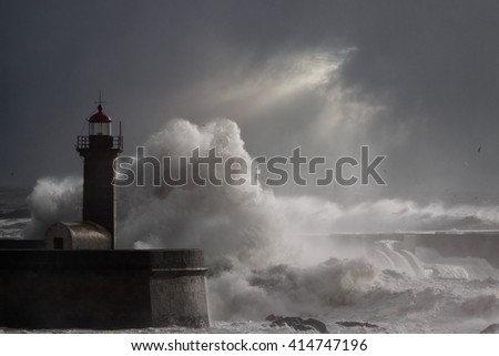 Dramatic seascape with big stormy waves over lighthouse in a cloudy winter noon with sunbeams. Enhanced sky.