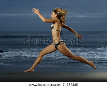 Dramatic shot of beautiful young woman in bikini running on the beach - stock photo