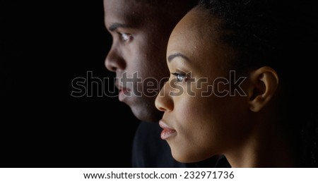 Dramatic side view of two young African American people on black background - stock photo