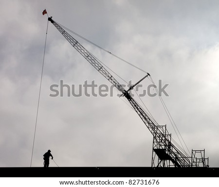 Dramatic Silhouette of Steel Worker and Crane at Construction Site