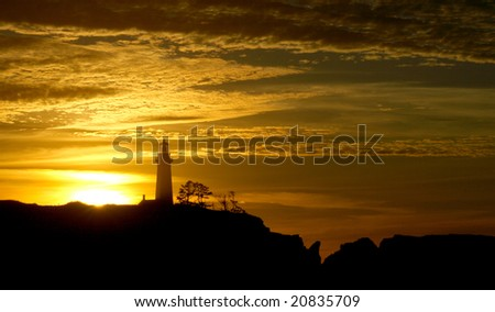 Dramatic skies during a sunset silhouettes Yaquina head lighthouse. - stock photo