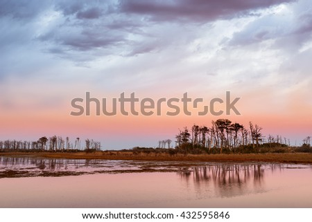 Dramatic Sky Along Coastal Inlet at Sunset - stock photo