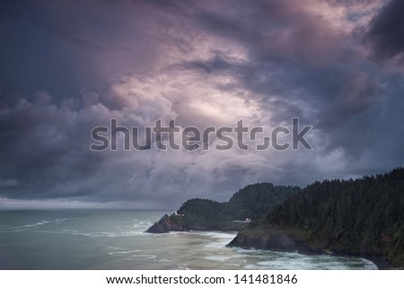 Dramatic sky at dusk hang over the Heceta Head Lighthouse off Oregon's coast - stock photo