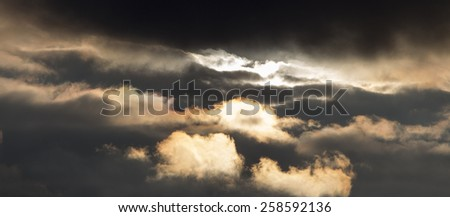 Dramatic sky at sunset.The storm sky in rays of the setting sun. Cold dramatic decline. - stock photo