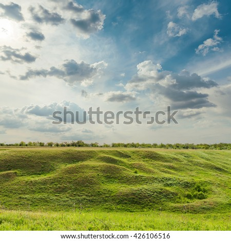 dramatic sky over green meadow - stock photo